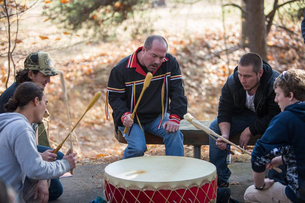 A photo of several people beating a drum and singing