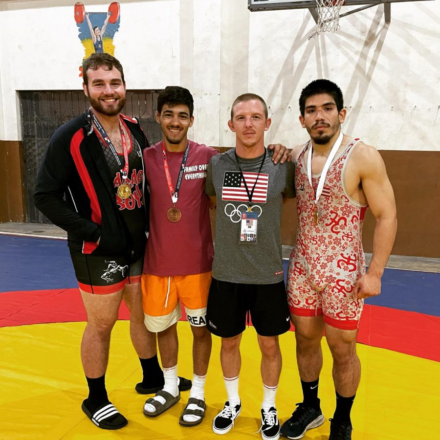 SUCCESS OUTSIDE THE U.S.—NMU Greco-Roman Wrestling volunteer assistant coach Paul Tellgren poses with the three medalists Maxwell Diaz, Diego Romero and Jovan-Antonio Mercado. All three took home medals at the Eduardo Campbell Cup in Santiago, Panama on September 4. Photo courtesy of Paul Tellgren.