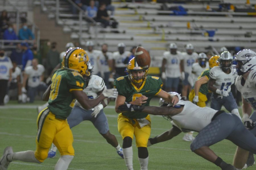 CARDIAC CATS—NMU quarterback Drake Davis pitches the ball while being tackled to wide receiver Tyquan Cox during Saturdays 28-24 loss to Grand Valley State. Travis Nelson/NW