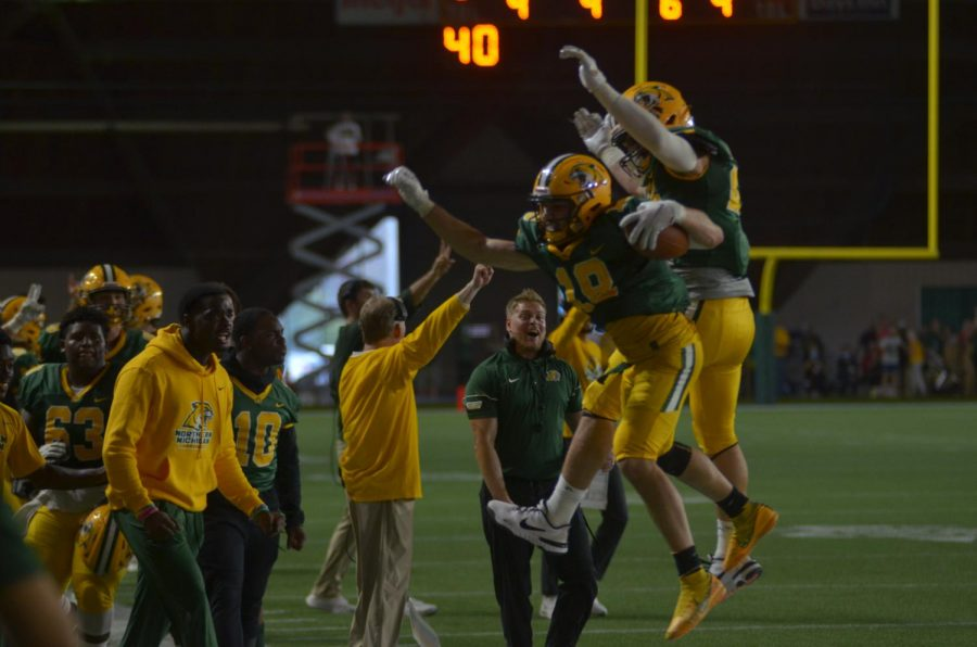 WRAPPING UP THE WEEKEND—The NMU football team celebrates on the sidelines in the fourth quarter of its game against Wayne State on Saturday, Oct. 2. However, the Cats football team fell on the road to Davenport 18-13 to drop to 1-1 in conference play. Travis Nelson/NW