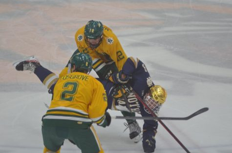 LUCK OF THE IRISH—NMU forward Connor Marritt and defenseman Trevor Cosgrove collide with Notre Dame forward Grant Silianoff in the first period of Saturday nights game. The Cats came up short 5-2 against the Fighting Irish, and didnt get good bounces throughout the game. Travis Nelson/NW
