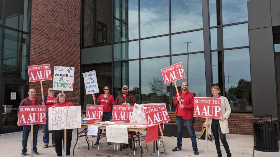 RED IS THE NEW GOLD—Members of the faculty union, AAUP, stand outside of the Northern Center on Friday to protest against the ongoing contract negotiation mediation.