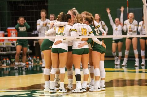 HOME SWEET HOME— The NMU Volleyball team huddles up after scoring a point while the bench celebrates behind them. A few of NMUs sports teams had an eventful weekend at home for homecoming. Photo courtesy of NMU Athletics